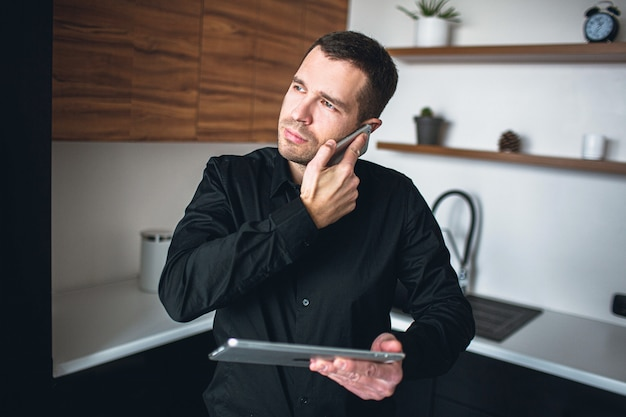 Young entrepreneur or businessman talking on phone or has business conversation. sand in kitchen alone with tablet in hands. manage company or business. look to left. concentrated and confident man.