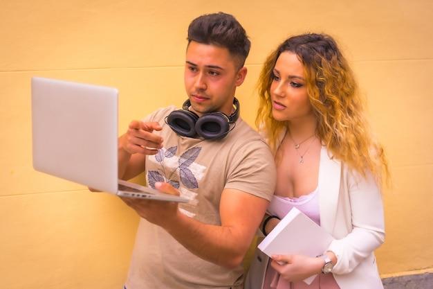 Пара молодых предпринимателей, работа в команде с компьютером. с желтым фоном