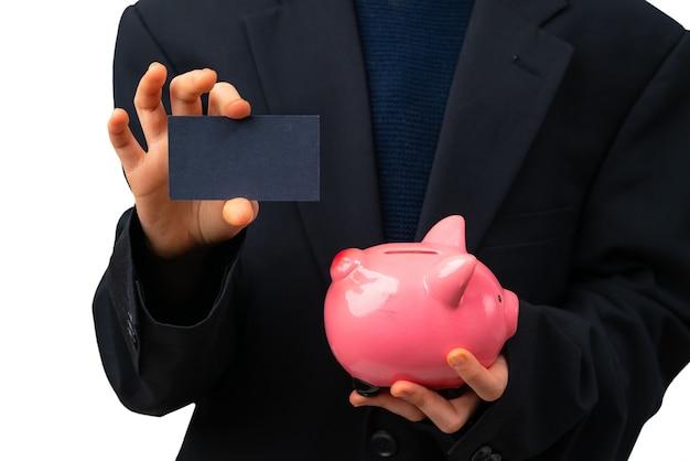 Молодой предприниматель, держа визитную карточку рядом с копилкой. финансовое образование для детей.