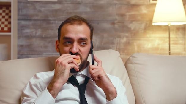 Молодой предприниматель в строгой одежде ест гамбургер во время делового разговора по телефону.