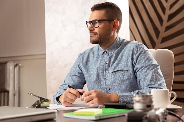 自宅で働く眼鏡とシャツを持つ若い起業家の男