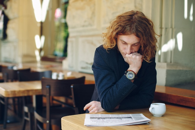 カフェで新聞を読む若い起業家