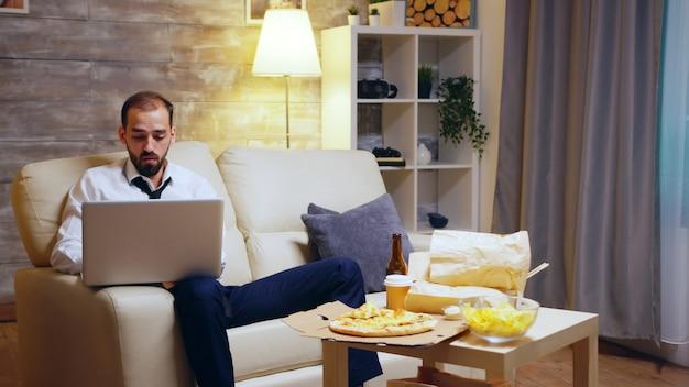Молодой предприниматель, сидя на диване, работает на ноутбуке и пьет пиво.