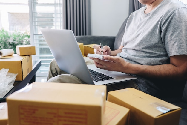 Young entrepreneur sme freelance man working with note packaging sort box delivery online market