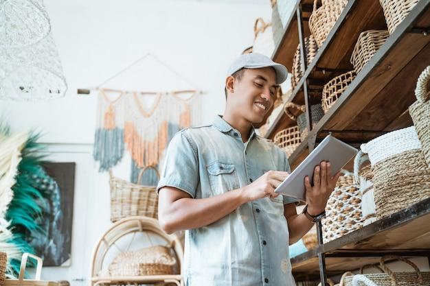 クラフトショップに立ってデジタルタブレットを持って若い起業家が微笑む