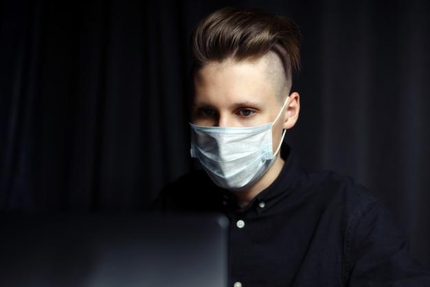 自宅で夕方に遠隔学習オンラインコースを勉強している若い起業家。コロナウイルスのパンデミックによる自己分離の概念