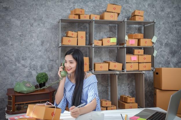 Молодой предприниматель разговаривает по телефону, как она сидит за своим столом в домашнем офисе.
