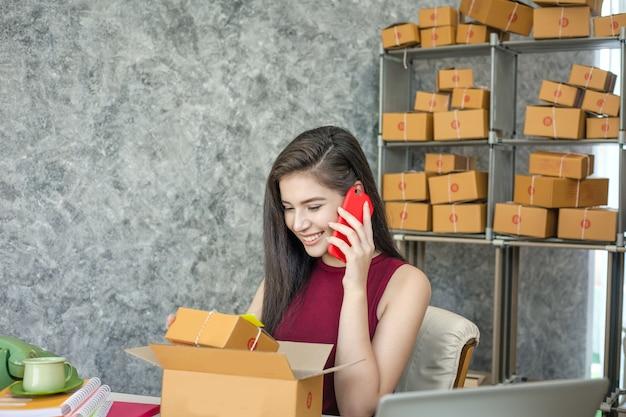 Молодой предприниматель разговаривает по телефону, когда она сидит за своим столом в домашнем офисе