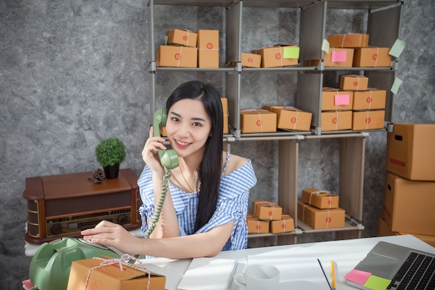 Young entrepreneur talking on a phone as she sits at her desk in a home office.