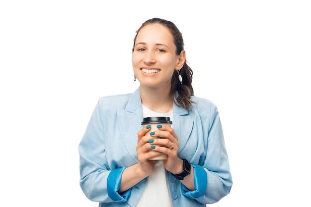 若い起業家、教師、またはビジネスウーマンは、持ち帰り用のコーヒーカップをしっかりと握っています。