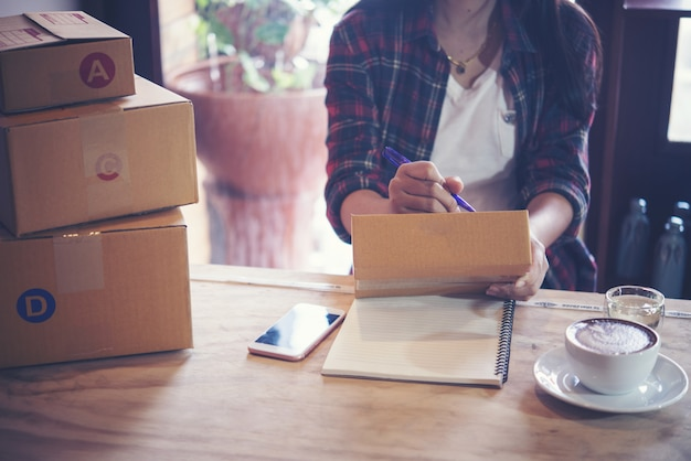 Young entrepreneur, teenager business owner work at home, box for delivery