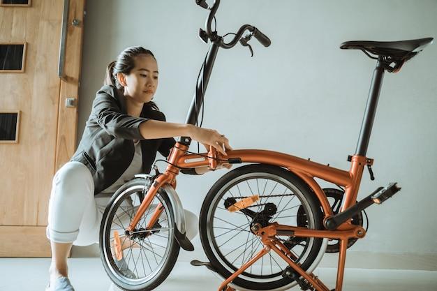 Молодая женщина-предприниматель готовит складной велосипед у себя дома
