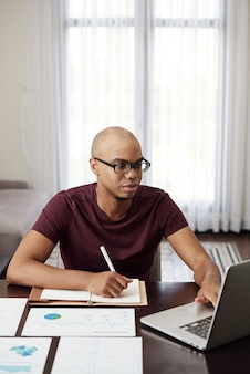 Young entrepreneur working from home, reading document on laptop and taking notes in planner