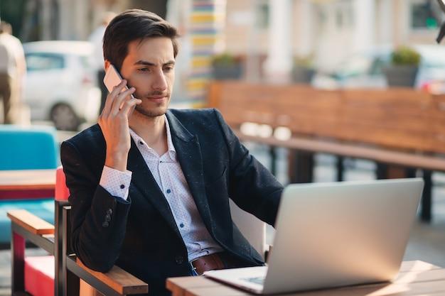 Молодой предприниматель работает на ноутбуке и телефоне