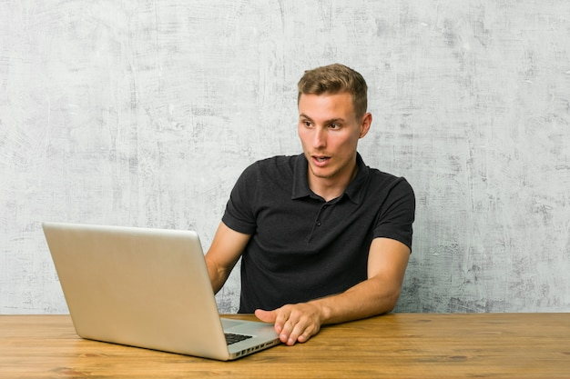 彼女が見た何かのためにショックを受けている机の上の彼のラップトップで働く若い起業家。