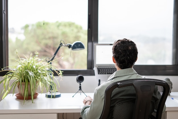 Young entrepreneur works from home in his office with the computer in front of a window