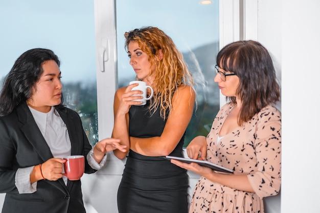 Молодая предпринимательская сессия в офисе, две молодые кавказские девушки и молодая латина в офисе на перерыве принимают чай