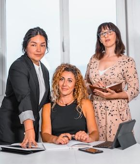 Молодая предпринимательская сессия в офисе, две молодые кавказские девушки и молодая латина в офисе готовят встречу