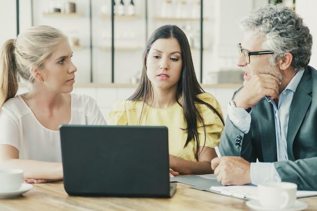 Молодые предприниматели и зрелый инвестор смотрят презентацию и обсуждают проект.