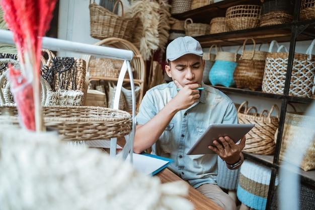 若い起業家は、手作りのタブレット画面を見ることを切望し、躊躇しています