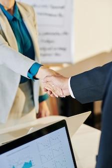Молодые предприниматели пожимают друг другу руки после заключения сделки и обсуждают детали сотрудничества