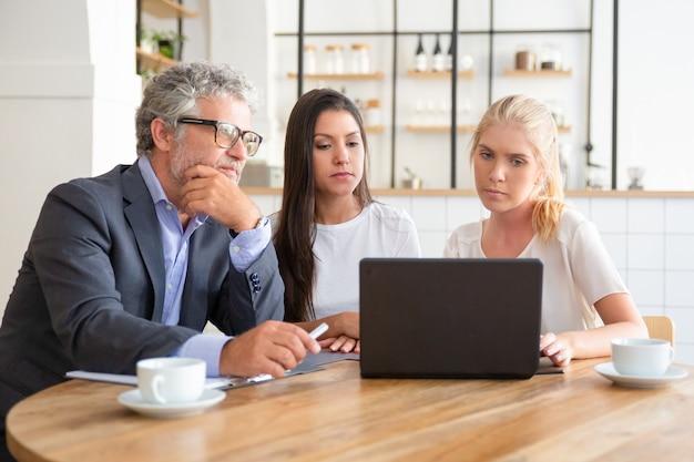 Молодые предприниматели показывают презентацию зрелому инвестору