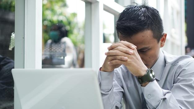 젊은 기업가는 노트북과 함께 앉아있는 동안 생각