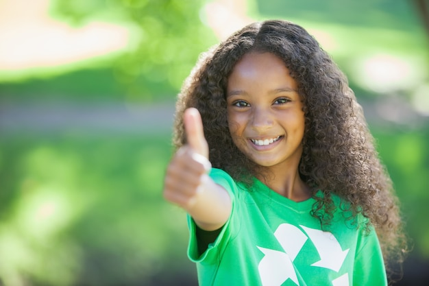 Young environmental activist smiling at the camera showing thumbs up