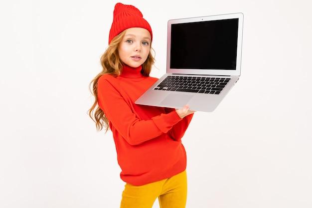 Молодая eoropean девушка в красной шляпе показывает экран ноутбука