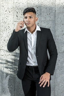 Young ethnic businessman speaking on smartphone