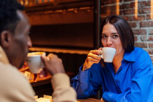 コーヒーショップでコーヒーを飲む若い民族カップル