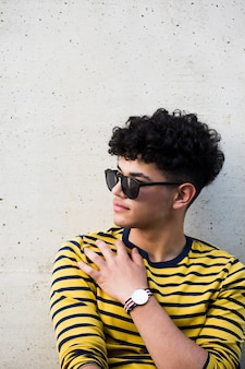 Young ethnic curly man in sunglasses and striped sweatshirt