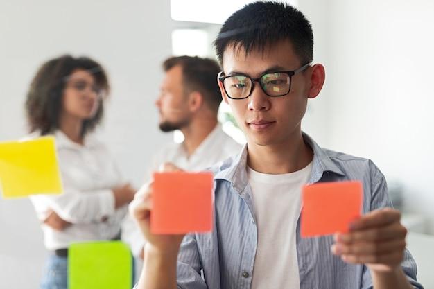 Молодой этнический мужчина в повседневной одежде и очках кладет бумажные стикеры на стеклянную стену во время встречи с коллегами по стартапу и обсуждения бизнес-стратегии