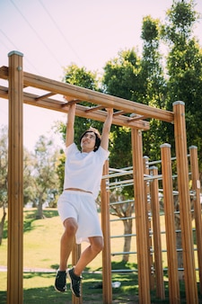 Young ethnic male in white clothes hanging on monkey bars
