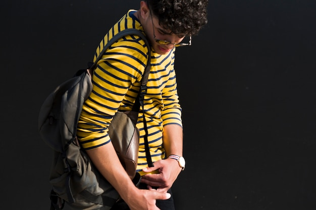 Young ethnic male with curly hair and backpack in striped shirt looking back down