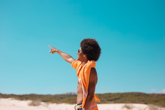 Young ethnic man showing finger forward on beach