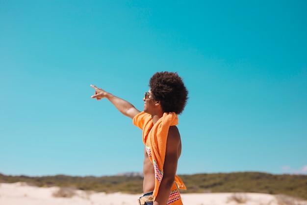 Молодой этнический человек, показывая пальцем вперед на пляже