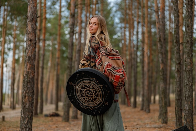 Young ethnic mature shaman female is walking and playing drums meditative music