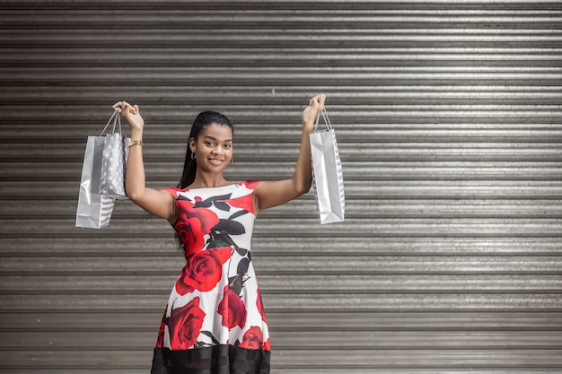 Young ethnic woman delighting in bags with purchases