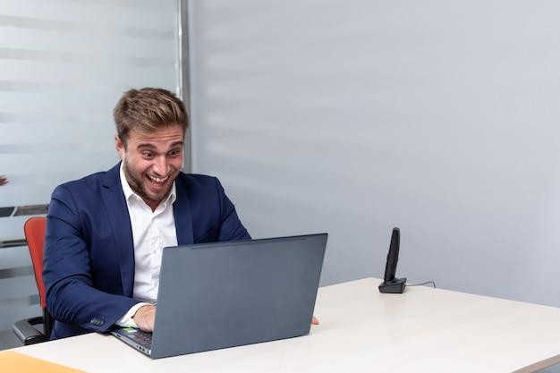 Молодой эйфорический бизнесмен делает видеозвонок в офисе.