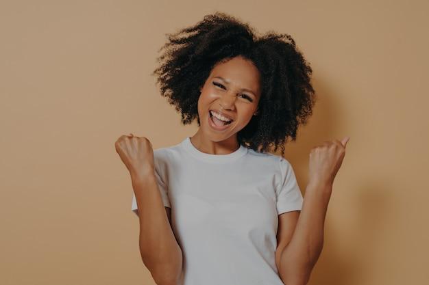 拳を食いしばって達成を祝う白いtシャツを着た若い陶酔感のある幸せなアフリカ系アメリカ人女性、黄色の背景に孤立してポーズをとっている間、イエスのジェスチャーをする大喜びの暗い肌の女性