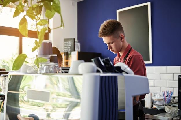カフェテリアのバーカウンターの後ろで仕事中の若いヨーロッパのバリスタ
