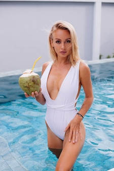 Young european blonde hair fit woman in white swimsuit stands in light blue color swimming pool natural day light holds coconut plastic straw