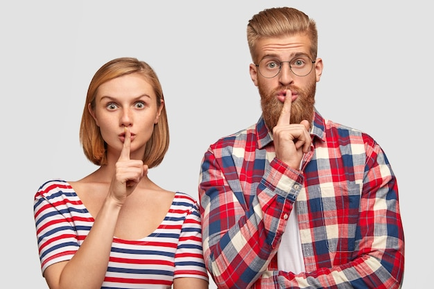 Giovane ragazzo e ragazza europei, mostra il segno del silenzio, guarda con espressioni sorprese, dimostra il gesto di silenzio