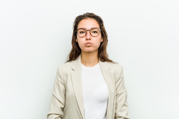 Young european business woman blows cheeks, has tired expression. facial expression .