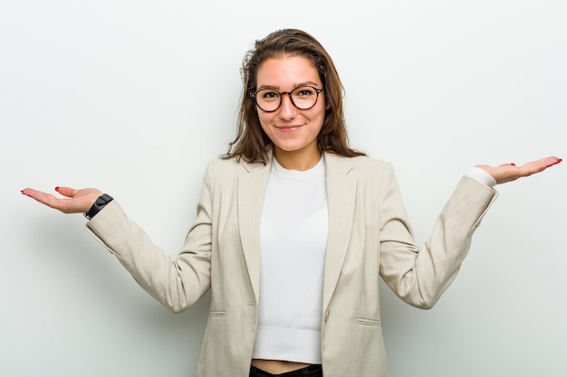 Young european business woman doubting and shrugging her shoulders in questioning gesture.