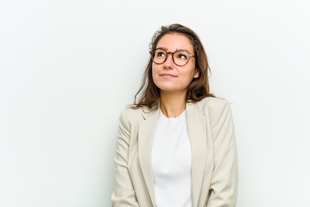 Young european business woman dreaming of achieving goals and purposes