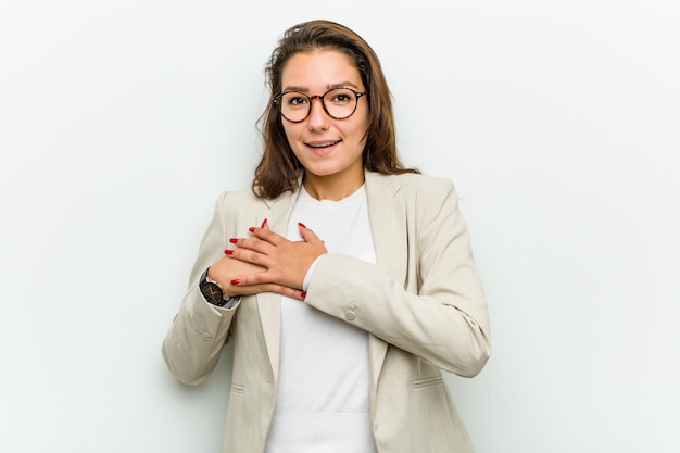 Young european business woman has friendly expression, pressing palm to chest. love concept.