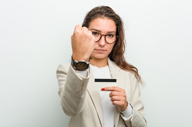 Young european business woman holding a credit card showing fist