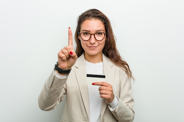 Young european business woman holding a credit card showing number one with finger.